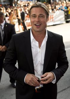 """Actor Brad Pitt poses for photographs on the red carpet at the gala for the new movie """"12 Years a Slave"""" during the 2013 Toronto International Film Festival in Toronto."""