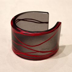 the current firework wide cuff features vibrant red yarn against black film, suspended in recycled resin.