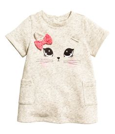 Light beige melange. Dress in sweatshirt fabric with a printed motif and appliqués at front. Snap fasteners at back of neck, short sleeves with sewn cuffs,