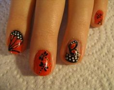 Who says short nails can't have as much fun as longer nails? Surely not this design! The black and white polish is used to create the butterflies' details and polka dots while the red polish serves as the base color and the shade of the wings itself. More shapes and curves as also added for effect.