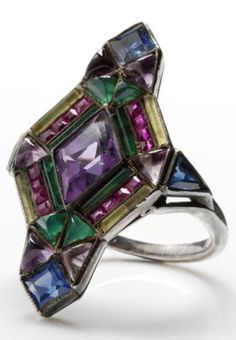 An Art Deco silver and gem-set ring, by Sibyl Dunlop, English, circa 1930. Set with amethysts, sapphires, green and yellow chalcedony. This ring illustrates Dunlop's flair for combining stones of vivid colours, and it unites the Arts and Crafts Movement's love of unfaceted stones with the geometric lines of Art Deco.