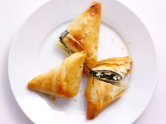 For a Healthy Appetizer, Make Air Fryer Spanakopita Bites | Is there anything your air fryer can't do? Soup, probably. It would be terrible at soup. But it can rock out these super-crunchy spanakopita bites! These savory Greek phyllo pastries are filled with spinach and salty cheeses with just a little hit of lemon and heat. Classic spanakopita calls for brushing the phyllo with butter; this version calls for olive oil, which adds even more Greek flavor.