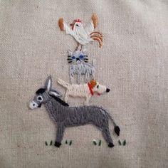 グリム童話の物語「ブレーメンの音楽隊」の場面を 手刺繍でブローチに仕上げました♪ロバの上にイヌ、ネコ、ニワトリがのり 泥棒達に「お化け」に間違われる楽しいシーン を表現した刺繍のポーチです。ロバの足下には草が小さくステッチされております。 裏側には可愛らしい森のお家がステッチされています。サイドには丸いクリアービーズのついたタッセルが あしらわれています。口金はアンティークゴールド色で、 外布はサンドカラーの綿布を使用し、 内側の布の色はアイボリーの綿布となっております。タオルハンカチやミラー、お化粧品を少々いれるのに 使いやすい大きさに作られておりますので プレゼントなどにも最適です。サイズ 縦:約14.5cm(口金含まず)×横:18.5cm(口金含まず)幅:5cm   5mmほど前後する事があります。口金を含むと縦は約15cmになります。   ※手刺繍ですので、それぞれに個性があります。  多少イメージ写真との差異がありますのでご了承ください。