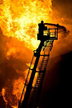A fire fighter fighting a fire from on top of a tall ladder.