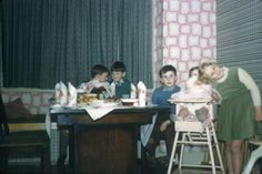 Colour transparency slide of (from the left) Jim Turner, two unidentified boys, Jayne Turner in a highchair and Dorothy and Ken Perrin's daughter beside her, around a dining table laid out for a tea party, in the front room of the Turner family home at 182 Whittington Way, Pinner, Middlesex. The photograph was taken by Selwyn Turner in 1958. This is one item in the Documenting Homes collection (168/2011-1 to –85) from Alec Turner. Object type:	transpa