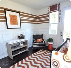 Striped walls.  Roman shade with accent trim. Upholstered sofa table with nailhead trim, used as changing table.