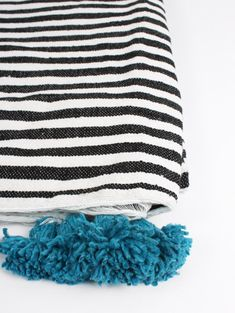 Handwoven cotton Berber Pom Pom blanket in black and white stripe with bright blue bobbles from Bohemia Design, made in Morocco.