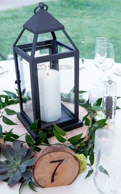 Deconstructed rustic floral centerpiece - wood slab with black lantern, greenery, white and green roses, succulents, and wooden table number. Wooden Slab Centerpiece, Rustic Lantern Centerpieces, Black Centerpieces, Rustic Lanterns, White Lanterns, Wedding Table Centerpieces, Wedding Tables, Wedding Ideas, Wedding Decoration