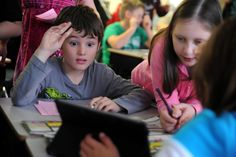 """Fourth grader Colin Housman, 9, helps decode a message during a """"mission to Mars"""" activity Jan. 28 at Odyssey Elementary School in Falcon School District 49. Housman was coordinating with the fourth grade classroom's three student communications officers for a shuttle recovery mission, a curriculum remotely hosted by Challenger Learning Center of Colorado in Colorado Springs. Using an Apple iPad, the students relayed data to the center."""