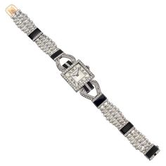 Cartier Lady's Platinum, Diamond & Onyx Art Deco Bracelet Watch. Cartier lady's Art Deco bracelet watch, featuring a manual-wind movement, silvered dial with black Roman numerals and minute track, as well as blued-steel hands,19mm, rectangular platinum case, the bezel set with round diamonds, on a fine five-row platinum and seed pearl trellis bracelet with diamond-set and carved black onyx stations and matching elegant attachment to case. c 1920s