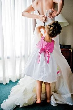 Flower girl helping zip up the Brides dress