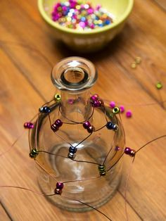 How to Make a Tequila-Bottle Hummingbird Feeder: Continue to crisscross, twist five times, thread the beads, separate wire, and repeat until the bottle is encapsulated in the wire and bead cage. Make sure you twist tightly for a clean appearance on all twists and to be consistent throughout the project. From DIYnetwork.com