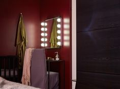 Pohled přes postel na působivě osvícené zrcadlo.