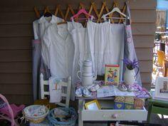 Racó de puntes blanques ,en preciosos vestits antics .I taula de cuina blanca milulu,treballada amb puntes ,teles i hule amb quadrets i flors .I altres objectes de decoració