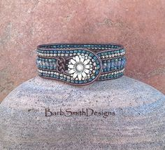 The Prairie Princess in Montana Blue  This enchanting cuff bracelet features a center row of beautiful 4mm faceted fire-polished smoky Montana Blue glass beads surrounded by Opaque Picasso seed beads in Montana Matte Blue. The two outer rows are stitched in Nickel finished Toho and Montana Blue seed beads. The Prairie Princess is adorned with a daisy metal antique silver button and stitched on Metallic Brown Indian leather cord surrounded by a beaded button hole adorned with a Josephine Knot…