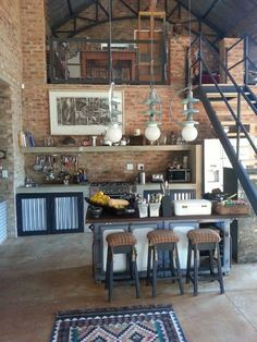 Brick apartment with mezzanine. Take those tassels off the stools and use more rugs. It has a cool vibe.