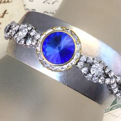 We embellished this metal cuff bracelet with vintage rhinestones, including a beautiful blue rivoli rhinestone accent!