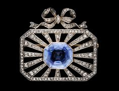 A Belle Epoque Platinum, Diamond, & Blue Sapphire Brooch, ca 1900.