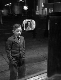 Boy watching TV on store window set, with the glass reflecting the TV screen. Photograph by Ralph Morse. Erie, Pennsylvania, USA, March 1949.