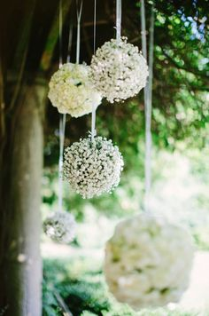White pomanders drip from tree branches creating an enchanted feel to this wedding. #babybreathwedding #weddingdecoration