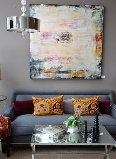 Grey walls, amazing art and vibrant cushions! All what I would consider 'different styles' yet they work so well together.