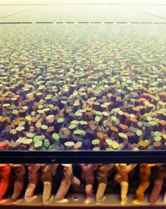 """FLOOR INSTALLATION BY DO HO SUH The installation takes of thousands of multicolored plastic toy figures """"holding up a large glass plate that can hold the weight of people across the glass."""""""