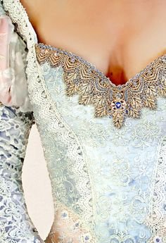 CINDERELLA'S GOWN  Cinderella's Gown is a sugary sweet ball gown with a tri-colored corset covered in heavily beaded laces, hand beaded trims, brooches, and delicate trims. Pastel colors and soft silks complete this exceptional gown.