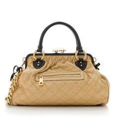 Launched in 2005, the Marc Jacobs Stam was named in honor of Canadian model, Jessica Stam. This iconic satchel is made from quilted gold canvas with black leather trim and gold-tone hardware. Details include two rolled handles, a front pocket, kiss lock closure, and fully lined interior with one zippered pocket. Wear this style on the forearm or over the shoulder with a detachable strap.