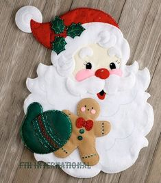 Bucilla ~ Santa's Treats ~ Felt Christmas Wall Hanging Kit Bucilla felt applique kits are a Christmas tradition. This Santa's Treats wall hanging kit features a large Jolly Santa face with Santa holding a brightly decorated Gingerbread Man in his hand. Felt Christmas Ornaments, Noel Christmas, Christmas Projects, Christmas Stockings, Christmas Decorations, Felt Wall Hanging, Christmas Wall Hangings, Santa Face, Felt Applique