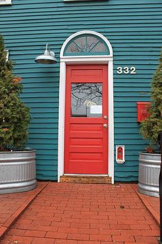 Curb appeal at its best! --Bright red, contrasting door color - check. --Smartly designed light fixture - check. --Bold house numbers - check. --Foliage that frames the door & draws your eye in - check. Yep, this is a door that beckons. Besides, who can resist a tiny fairy door?
