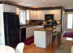 Contemporary Kitchen with Recessed beadboard panel cabinets, L-shaped kitchen with island, Black appliances