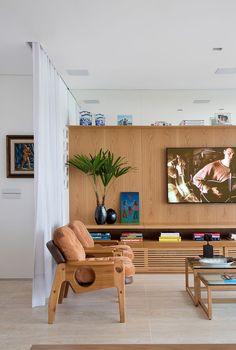 Decoração de apartamento. Sala de estar, luz natural, poltrona de madeira, mesa de centro com livros e adornos, rack de madeira com vaso com plantas, quadro e adornos. Prateleira de madeira com livros e adornos.    #decoracao #decor #details #casadevalentina