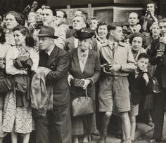 A photograph showing a crowd of people waiting to take a snapshot photograph, taken in 1950 by F Greaves for the Daily Herald.