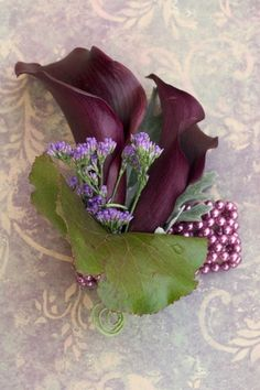 Wrist corsage made from mini calla lilies accented with misty blue on a purple beaded bracelet.