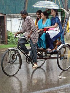 Women ride on a cycle rickshaw, shielding themselves from the rain with an umbrella, in Allahabad, India