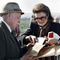 Jacqueline Kennedy Onassis, 57, attending the Piedmont Hunt's weekend of point-to-point horse racing on March 29, 1987, is obviously pleased with a packet of photos given her by Marshall Hawkins. He made the pictures of Mrs. Onassis over a period of years, going back to her days as First Lady. (UPI Photo/J. Dailey/Files)