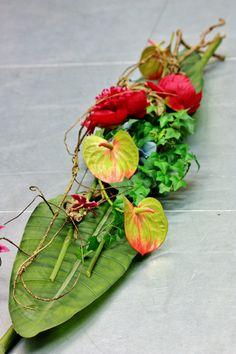 Sia school. Centro de mesa con dos hojas de strelitzia como base, dos peonías y dos anthuriums, un poco de yedra y escondido un poco de hydrangea. El toque rustico de la rama seca es imprescindible. Las flores hechas a mano no manchan en la mesa y se pueden reutilizar cuantas veces quieras