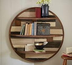 """Circular Planked Wood Shelf ($399) Merging the appeal of an artwork with the function of a shelf, this piece is a handsome home for favorite objects. The planked back is pieced and painted by hand in earthy colors. 36"""" diameter, 9"""" deep; Crafted of mango wood with a stained and distressed painted finish."""