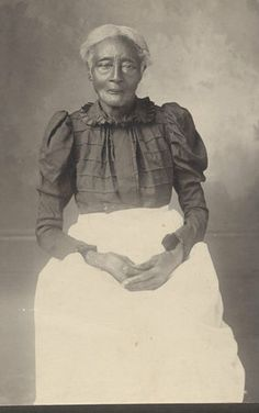 C1900 Texas, African American Woman, a Former Slave in this  Haunting Photograph.  She is wearing her best dress and a dazzling white apron and has a flower tucked into her sleeve.