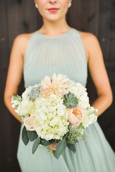 Bridesmaids wearing sage green dress and holding a peach coloured bouquet