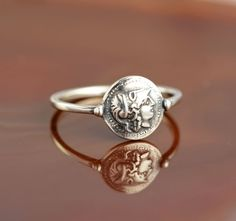 """""""Athena"""" is a delicate silver ring with an ancient coin representing the fearless goddess Athena, the archetype of the brave woman, boldly striding across life, whose greatest strength is her outstanding intelligence."""