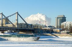 Ice trip - Pleasure boat sailing on a frozen river under the bridge metal structures, frosty sunny winter day on the background of residential and office buildings and power plant pipes, spewing steam - in Moscow, Russia