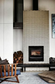 Feature wood burner, stacked logs and scandinavian arm chair.