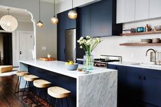 We often use dark navy as a neutral base because it can be a beautiful complement to other warmer tones, particularly wood, brass, and brick | archdigest.com