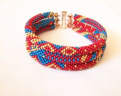 Was $60.00 Now $36.00    This bead crochet rope bracelet is made from seed beads in blue, red and gold. It will be perfect to create a unique look for