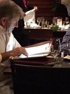 Restaurante escuro combinado com cardápio com letras pequenas = lanterna do celular para ajudar
