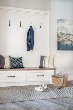 Gray and white mudroom with blue accents. Herringbone tile floor. Wainscoting.