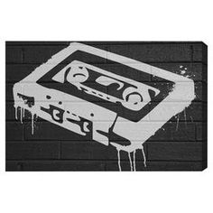 Equally at home in an artful collage or on its own as an eye-catching focal point, this hand-stretched canvas print showcases a graffiti-inspired cassette tape motif. Made in the USA.  Product: Canvas printConstruction Material: Fine art canvas and woodFeatures:  Hand-stretchedIncludes a certificate of authenticity by the artist  Made in the USA Arrives ready to hang with all hardware included    Cleaning and Care: Dust lightly using a soft, clean, lint-free cotton cloth