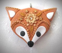 Polymer clay Fox pendant, handmade with applique technique, one of a kind. Light brown with white, black eyes and nose, with lacy decoration of flowers, leaves and dots in various shades of gold and a clear crystal. By Lis Shteindel.
