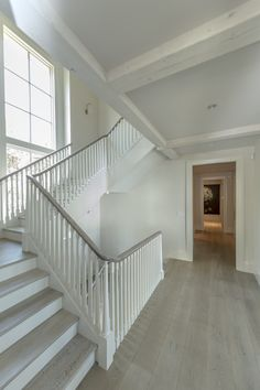 gray flooring Custom Designed staircase with stained oak hand railing. Floors throughout Exquisite Surfaces NYC - Blonde Manoir Gray Color Flooring For Stairs, Oak Stairs, White Stairs, Wood Staircase, House Stairs, Grey Flooring, Stair Railing, Staircase Design, Hand Railing